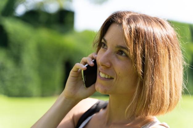 庭で携帯電話で話しているたてがみの半分を持つブロンドの女の子