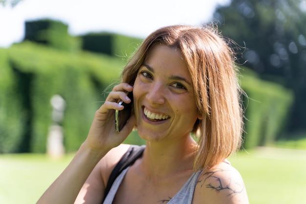 たてがみの半分が携帯電話で話し、屋外で笑っているブロンドの女の子。テクノロジーとライフスタイル