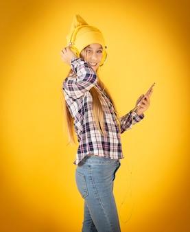 音楽を聞いている帽子とヘッドフォンを持つブロンドの女の子黄色