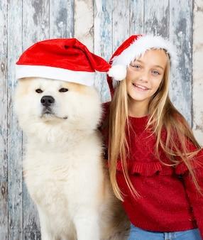 Блондинка с собакой в шляпе санта-клауса, празднование рождества деревянной стене