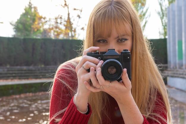 빈티지 카메라로 사진을 찍는 립스틱과 스웨터 금발 소녀