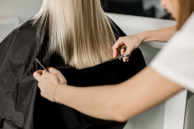 Blonde girl with long straight hair sits in a chair in a beauty salon. black robe. view from the back.