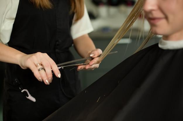 Блондинка с длинными прямыми волосами сидит в кресле в салоне красоты и подстригает волосы крупным планом