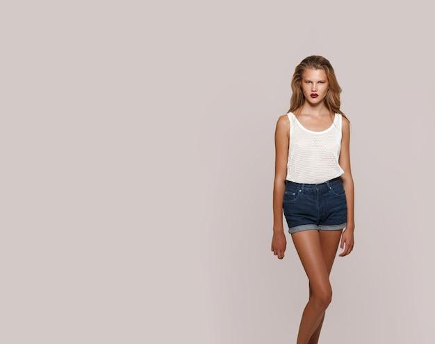 白いtシャツとデニムのショートパンツを着て、カメラを自信を持って、淡いピンクの背景で隔離のメイクアップのブロンドの女の子。テキスト用のスペース。