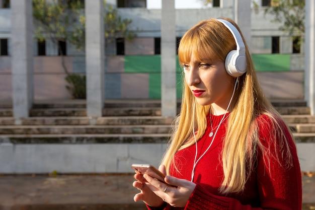 빨간 립스틱과 빨간 스웨터와 전화 및 공원에서 헤드폰으로 음악을 듣고 금발 소녀.