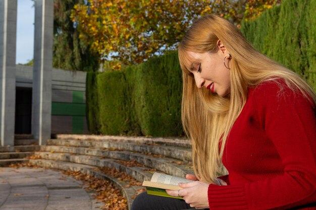 빨간 립스틱과 공원에서 책을 읽고 빨간 스웨터와 금발 소녀.