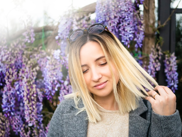 Blonde girl with round glasses on the background of spring wisteria.