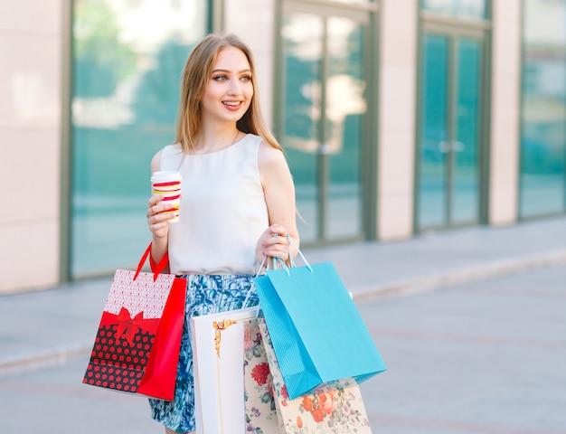 쇼핑 가방가 게에서 밖으로 걸어 금발 소녀.