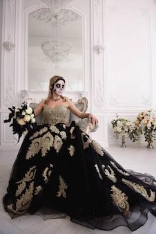 砂糖の頭蓋骨を作る、死者の日またはハロウィーンのブロンドの女の子