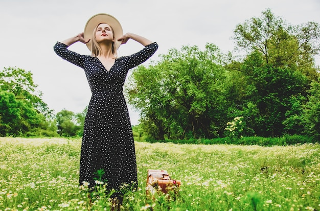 Blonde girl with suitcase and hat in chamomiles flowers field in summer time