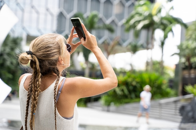 サングラスと白いタンクトップといくつかの近代的な建物に彼女の携帯電話で写真を撮る三つ編みのブロンドの女の子