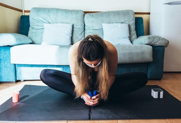 Блондинка с хирургической маской занимается йогой и медитацией дома.