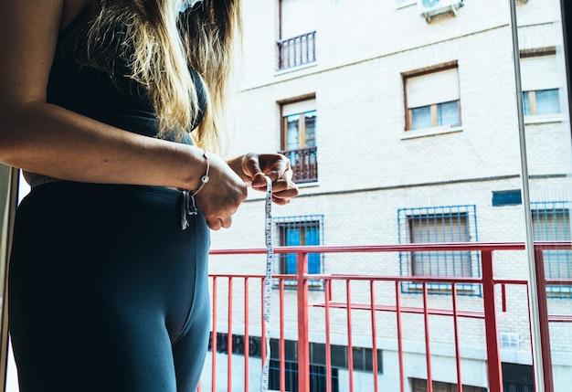 집에서 스포츠 후 그녀의 허리를 측정하는 수술 마스크와 금발 소녀.