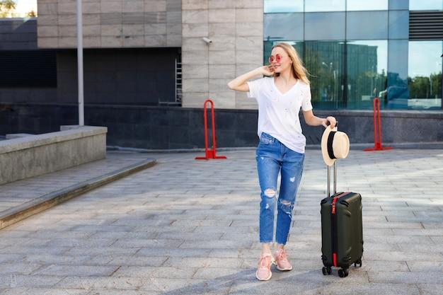 空港でバスの夏を待っている旅行バッグと麦わら帽子を持つブロンドの女の子