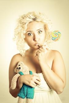 한 손에 다채로운 롤리팝을 들고 다른 손에는 곰 장난감을 들고 눈을 크게 뜨고 있는 금발 소녀