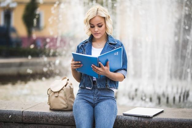 Блондинка студентка работает на своем портативном компьютере и читает книгу возле фонтана в городе днем