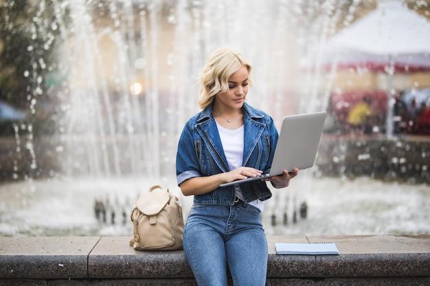 Блондинка девушка студентка работает на своем портативном компьютере возле фонтана в городе днем