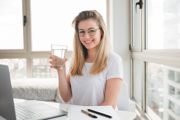 Blonde girl at work drinking water