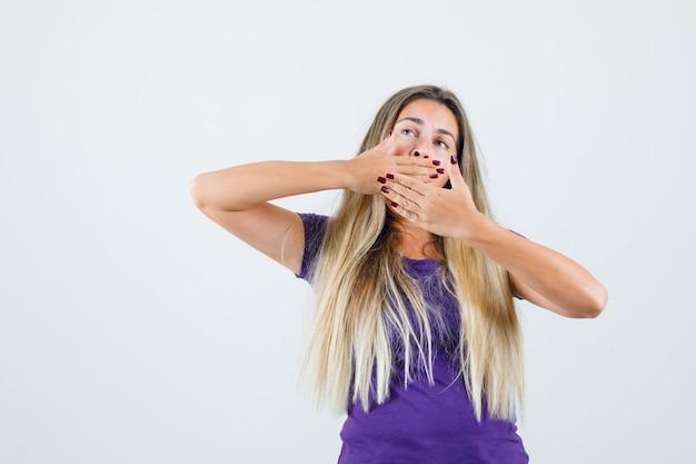 금발 소녀 하품과 보라색 티셔츠에 스트레칭과 졸린, 전면보기를 찾고.