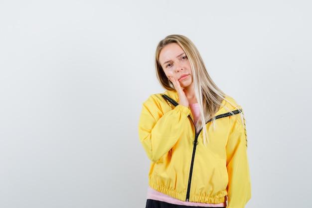 Ragazza bionda in giacca gialla che tiene la mano sulla guancia e sembra seria