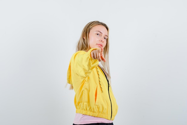 Ragazza bionda in giacca gialla che punta alla telecamera e sembra sicura