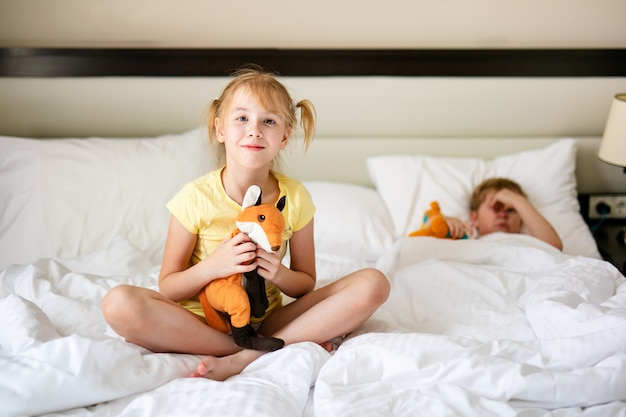 Blonde girl in yellow t-short and with toy orange fox in the white bed