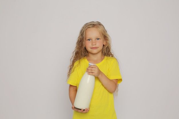A blonde girl in a yellow tshirt with a glass bottle of a blonde girl in a yellow ts in her hands