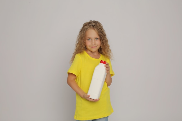 A blonde girl in a yellow tshirt with a plastic bottle of milk in her hands