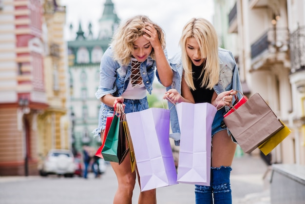 Blonde girls standing on street with bags