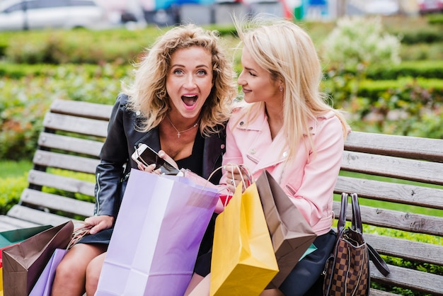 Blonde girls with shopping bags sitting