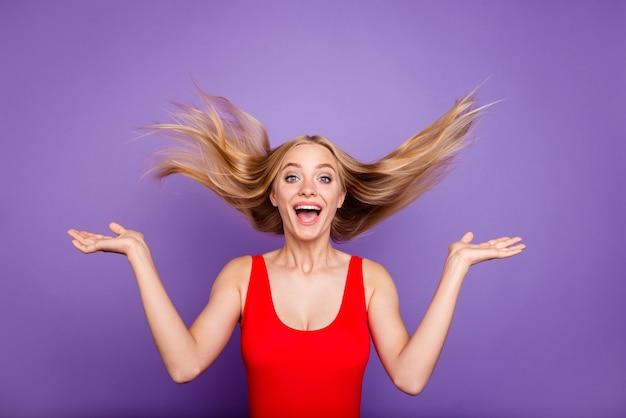空気を髪型を投げる赤い水着を着ている金髪のゴージャスな女の子