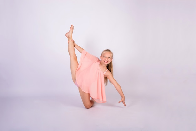 A blonde gymnast girl in a peach swimsuit stands in a gymnastic pose and looks at the camera on a white isolated wall