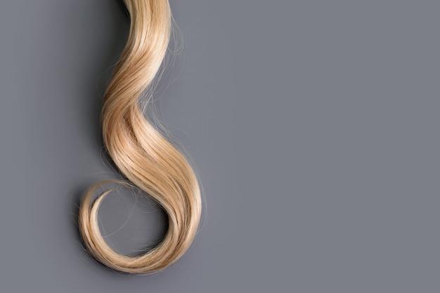 Кудри светлые волосы, изолированные на сером фоне