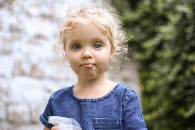 夏の外の庭で遊ぶブロンドの髪の少女