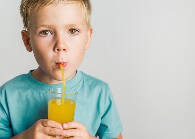 ブロンドの髪の子供がジュースを飲む