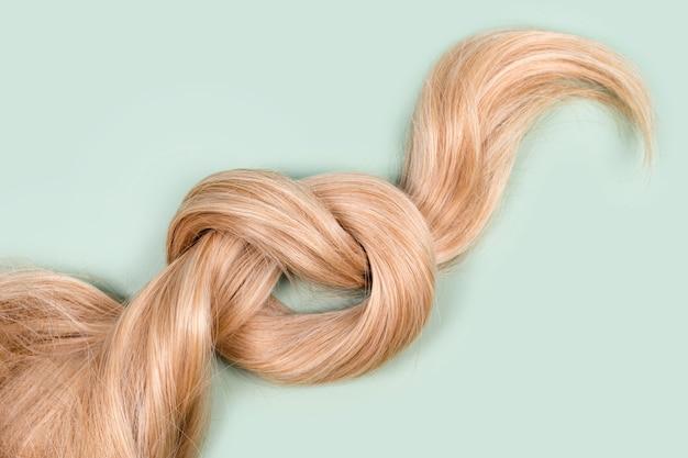 Прядь светлых волос завязана в узел. прядь медовых светлых волос на фоне мяты, вид сверху. услуги парикмахера, прочность волос, стрижка, прическа, покраска или окрашивание, наращивание волос, концепция лечения.