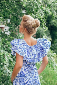 Blonde hair woman back with fashion hairstyle on summer garden background