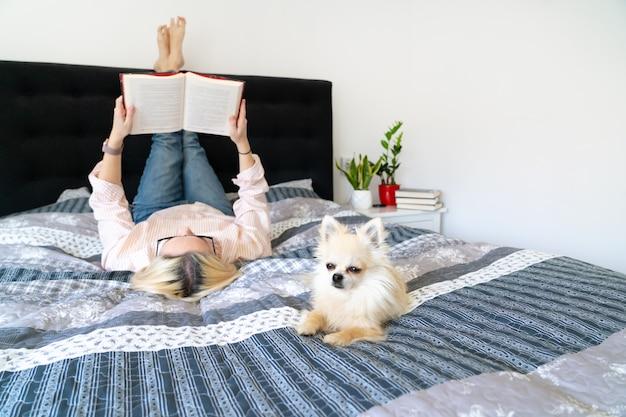 Светлые волосы женщина сидит на уютной кровати с собакой, держа открытую книгу и чтение. лежа женщина расслабляющий на диване у себя дома. концепция отдыха и комфорта людей. время для себя в карантине.