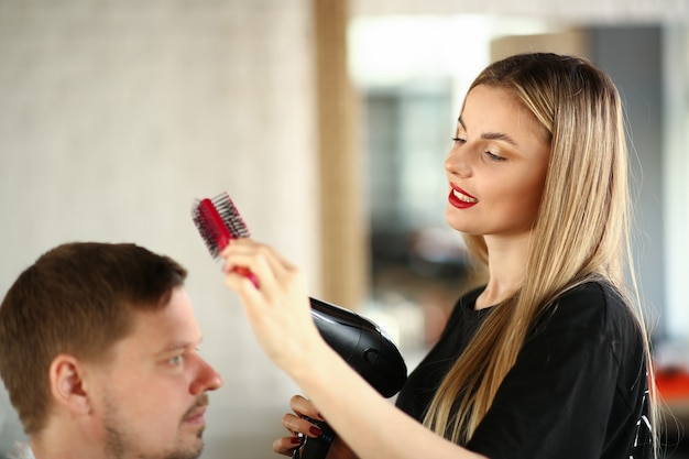 Blonde hairdresser using hairbrush for hairstyle