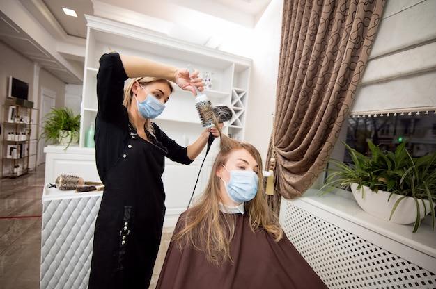 ヘアドライヤーでクライアントのブロンドの髪を乾燥させる医療用保護マスク付きのブロンドの美容師
