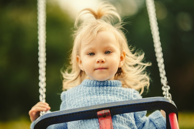 スイングのブロンドの髪の女の子