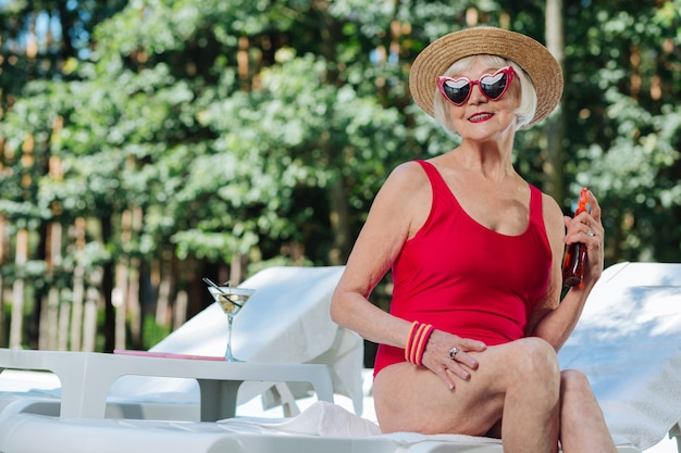 Blonde-haired grandmother wearing stylish accessories while sitting on deck chair waiting for husband