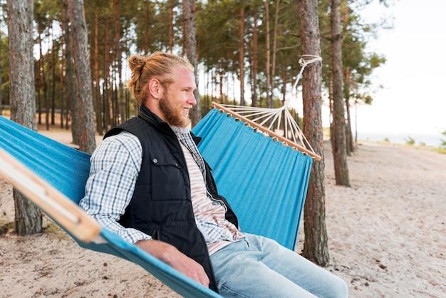 Светловолосый человек, сидящий на гамаке, вид сбоку