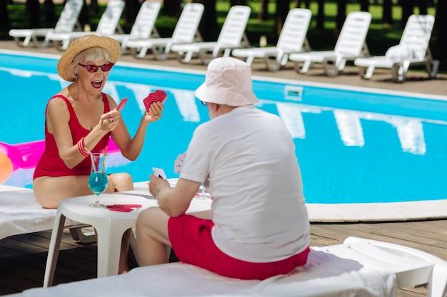 Светловолосая пенсионерка чувствует себя счастливой, выигрывая карточную игру, играя с мужем возле бассейна