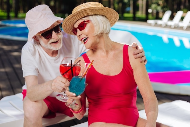 Blonde-haired retired woman listening to jokes of her husband while sunbathing near pool
