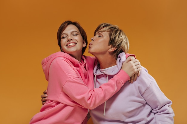 오렌지 배경에 밝은 분홍색 셔츠에 검은 짧은 머리와 그녀의 손녀를 키스 라일락 후드에 금발 머리 여자.