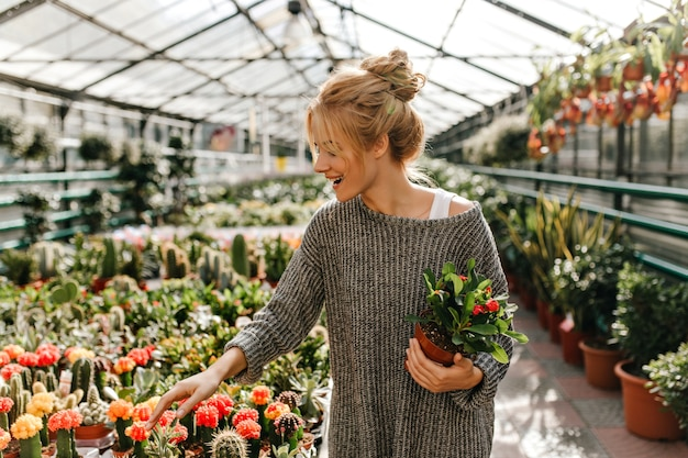 Blonde-haired woman with smile chooses cactus, holding beautiful plant in her hands.