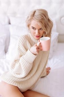 ブロンドの髪の女性。ピンクのお茶を保持しているベージュのセーターを着ている若い魅力的なブロンドの髪の女性 Premium写真
