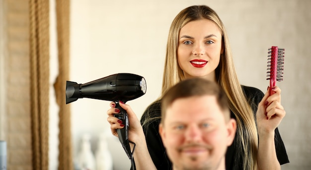 Blonde hairstylist using dryer and comb for man