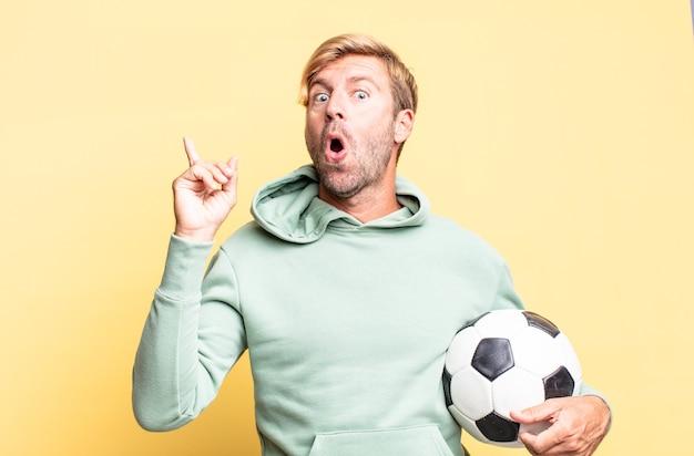 Блондинка красивый взрослый мужчина держит футбольный мяч
